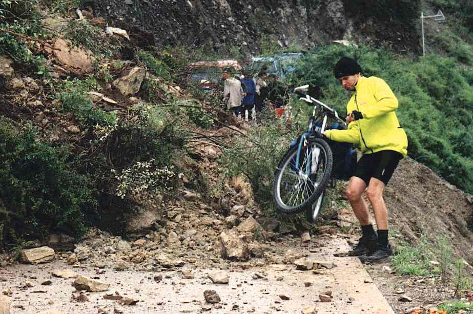 Mark carrying his bike over the landslide